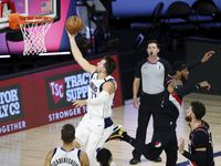 Dallas Mavericks guard Luka Doncic (77) shoots against the Portland Trail Blazers during the second half of an NBA basketball game Tuesday, Aug. 11, 2020, in Lake Buena Vista, Fla.
