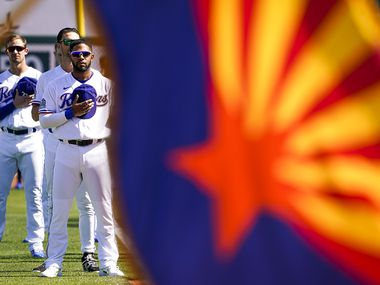 FILE - Rangers shortstop Elvis Andrus stands with teammates behind the Arizona state flag during the singing of the national anthem before a spring training game against the Kansas City Royals at Surprise Stadium on Tuesday, Feb. 25, 2020, in Surprise, Ariz.