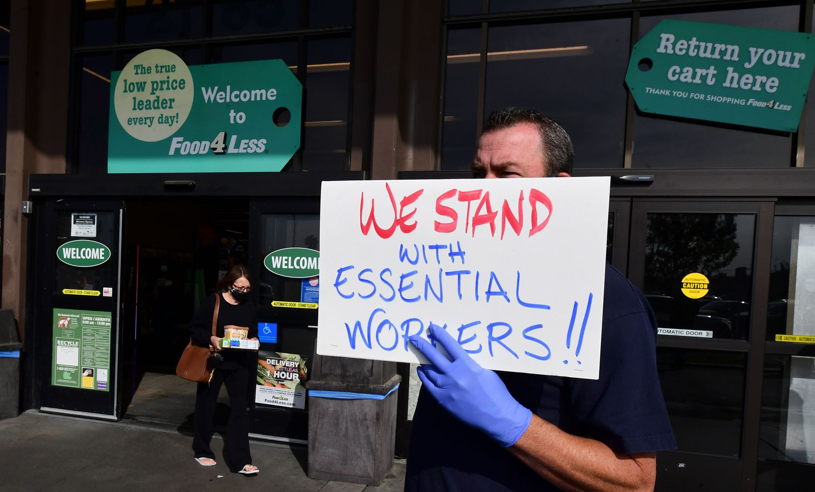 "Supermarket workers held placards in protest in front of a Food 4 Less supermarket in Long Beach, Calif., last week after a decision by owner Kroger to close two supermarkets rather than pay workers an additional $4 an hour in ""hazard pay"" for their continued work during the coronavirus pandemic."