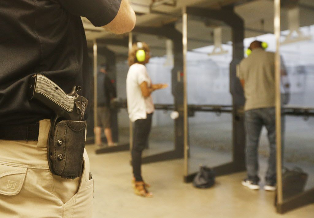 With his gun on his hip, instructor Mark Brushwiller watches shooters at the Frisco Gun Club in Frisco, Texas, Friday, April 17, 2015. (Michael Ainsworth/The Dallas Morning News)