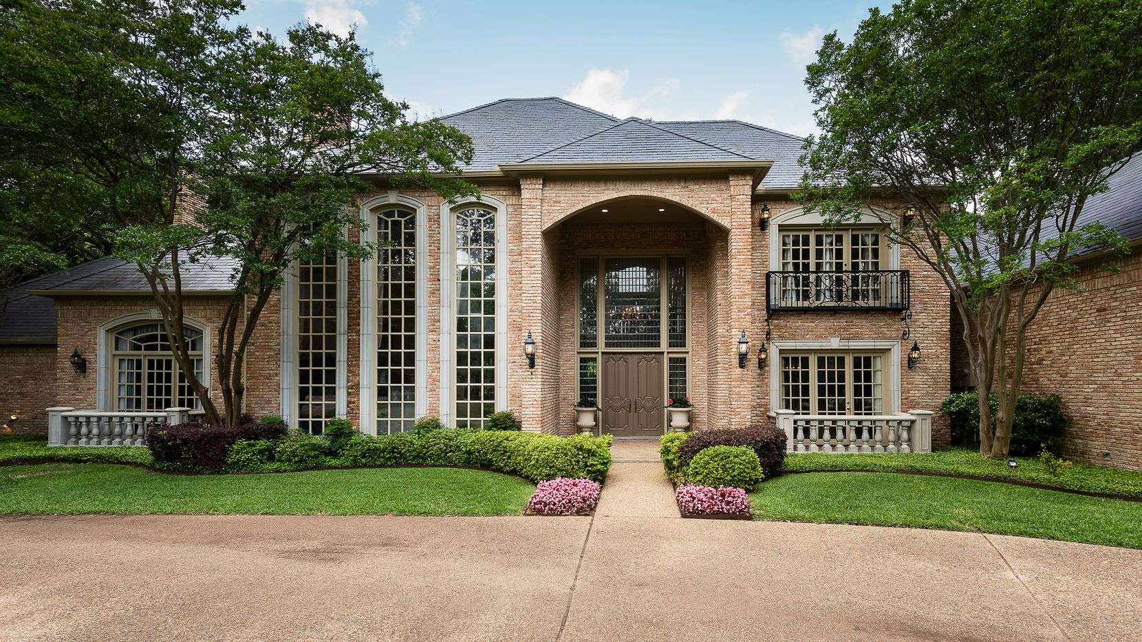 Take at the exterior of the house at 9441 Hollow Way Road in Dallas, TX.
