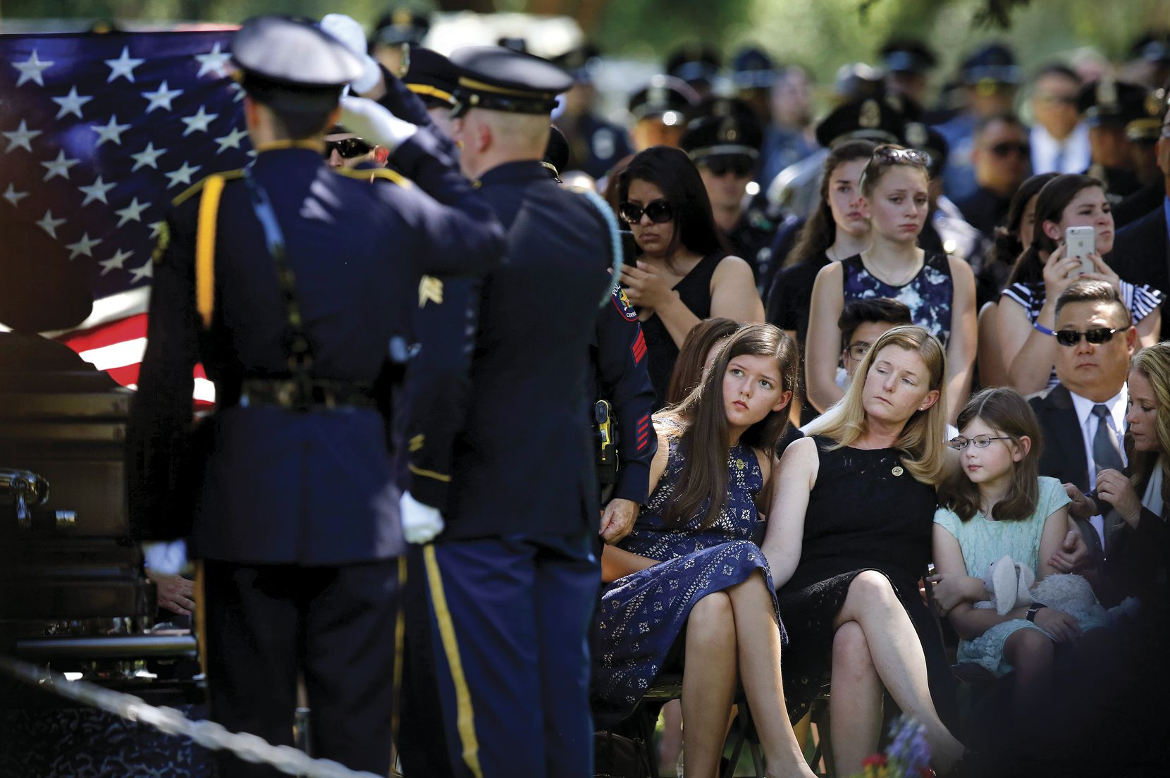 Heidi Smith and her daughters Victoria and Caroline were graveside as they laid her husband, Dallas police Sgt. Michael Smith, to rest at the Restland Funeral Home and Cemetery in Dallas on July 14. Smith was gunned down by Micah Johnson in the July 7 attack.