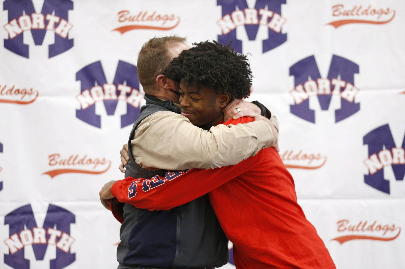 McKinney North wide receiver J.J. Henry gets a hug from McKinney North head coach Mike Fecci after signing his letter of intent to play for the University of Mississippi during a signing day ceremony at McKinney North High School on Wednesday, December 16, 2020 in McKinney, Texas. (Vernon Bryant/The Dallas Morning News)