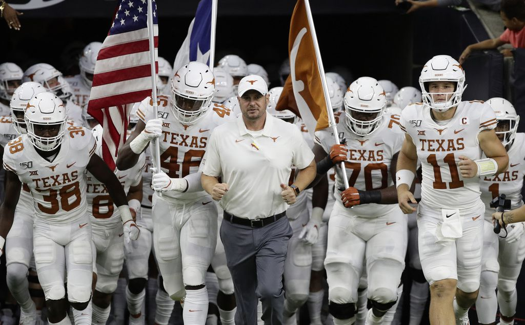 Texas head coach Tom Herman, center, takes the field with his team before an NCAA college football game against Rice Saturday, Sept. 14, 2019, in Houston.