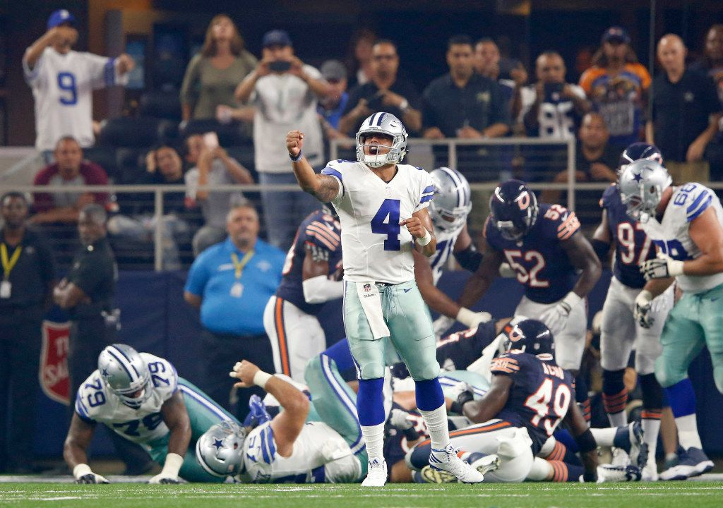 Dallas Cowboys quarterback Dak Prescott (4) celebrates after Dallas Cowboys running back Lance Dunbar (25) scored a touchdown on a run play in a game against the Chicago Bears during the first half of play at AT&T Stadium in Arlington on Sunday, September 25, 2016. (Vernon Bryant/The Dallas Morning News)