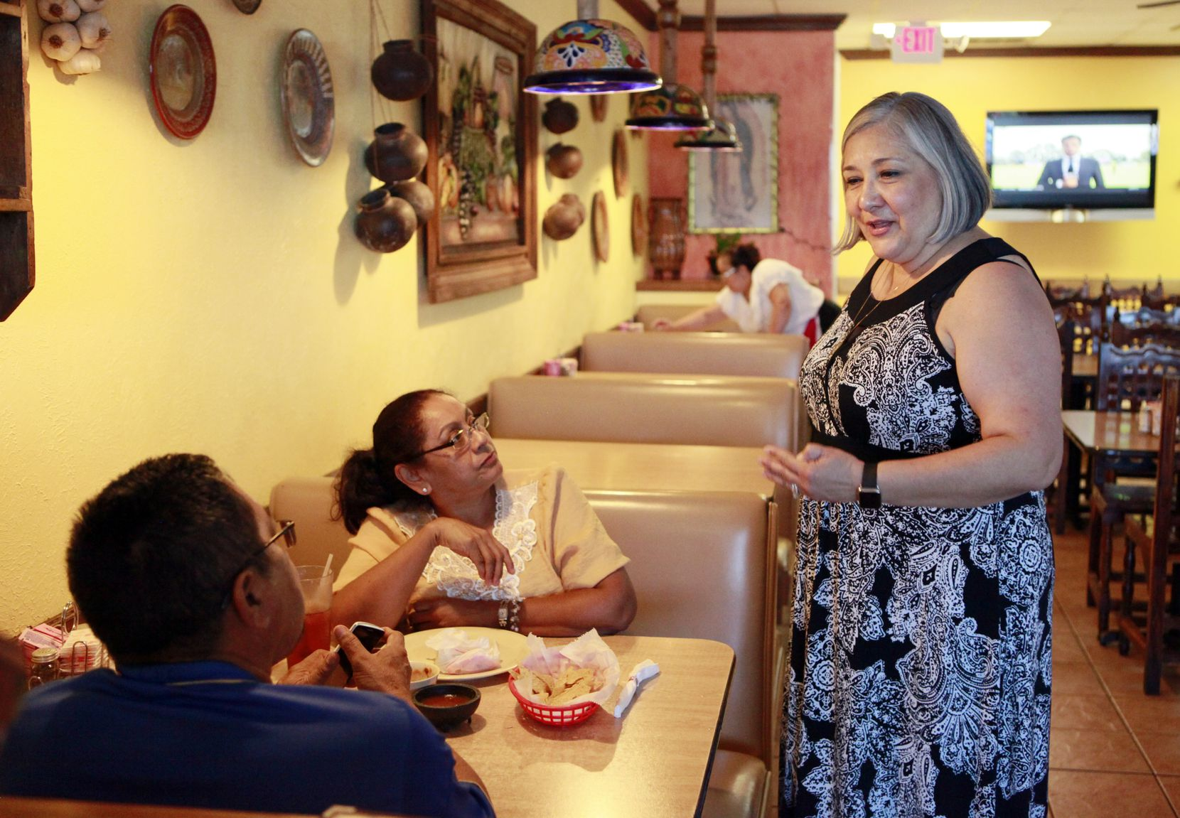 Elizabeth Villafranca, co-owner of Cuquitas Mexican restaurant in Farmers Branch, meets with customers Alejandra Osorio, left, and her husband Roman Osorio, on July 12, 2016.