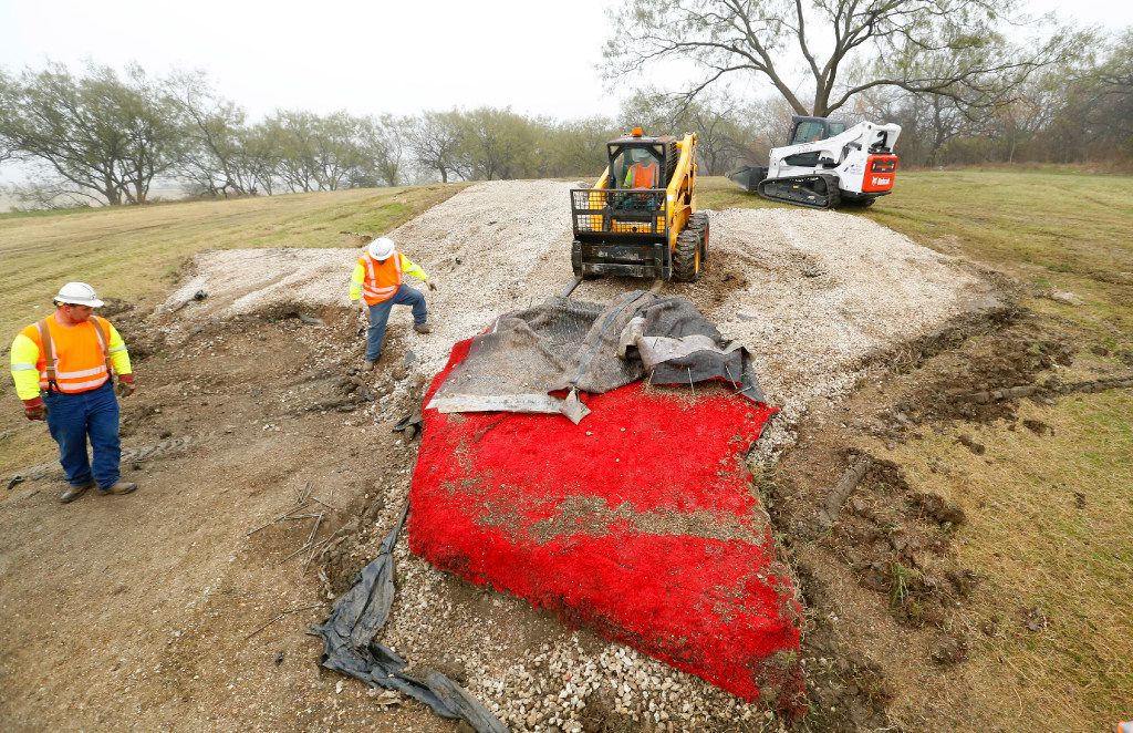 Texas Department of Transportation crews removed the red turf portion of the Texas-shaped sign on a hillside median off Interstate 20 between Mountain Creek Parkway and Spur 408 in southwest Dallas on Dec. 13, 2016.