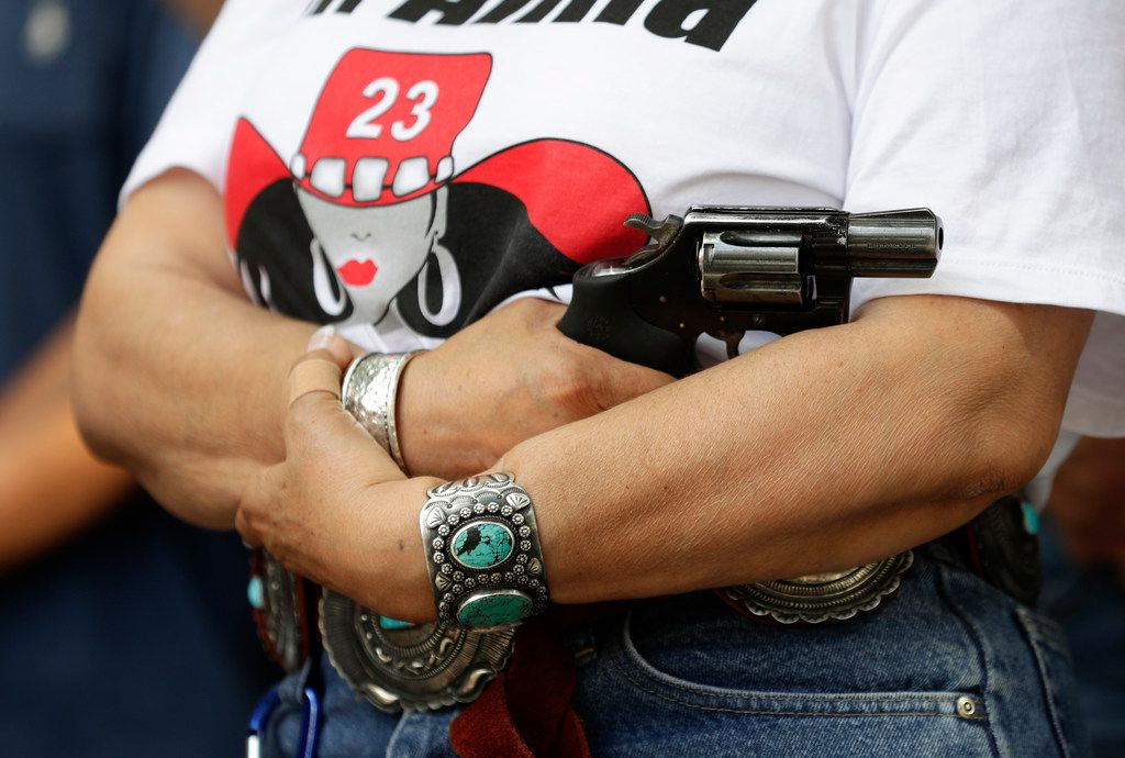 Dr. Alma Arredondo-Lynch holds a pistol as gun rights advocates gather outside the Texas Capitol where Texas Gov. Greg Abbott held a round table discussion, Thursday, Aug. 22, 2019, in Austin, Texas. State legislators passed 820 new laws this year, several of which expanded where, when and how Texans can carry their firearms.