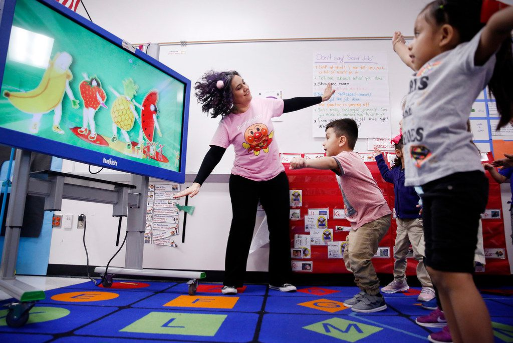 Pre-K teacher Patricia Sifuentes (left) leads a music and movement video lesson for her students, including  Ovet Martinez (center) and Altaira Cocom (right) at the newly-opened Arlington Park Early Childhood Center in Dallas, Wednesday, March 27, 2019.
