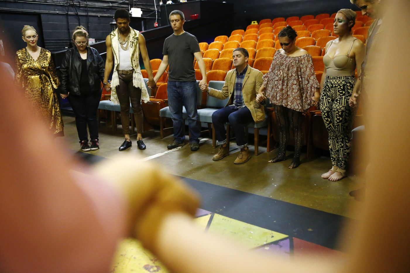 Director Derek Whitener (sitting) has a moment of silence with his troupe before opening night of Pippin.