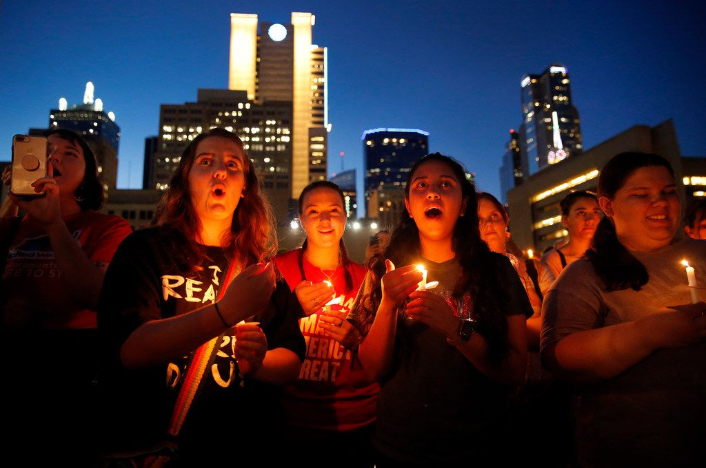 Denison, Texas friends (from center, left) Katy Schneider, Alison Earnhart and Kathia Suarez, chant with hundreds of others during the Lights for Liberty candlelight vigil outside Dallas City Hall, Friday evening, July 12, 2019. The group says they want to shine a light on the horrific abuses of the Trump administration in detention centers at the southern border, points of entry and across the country.