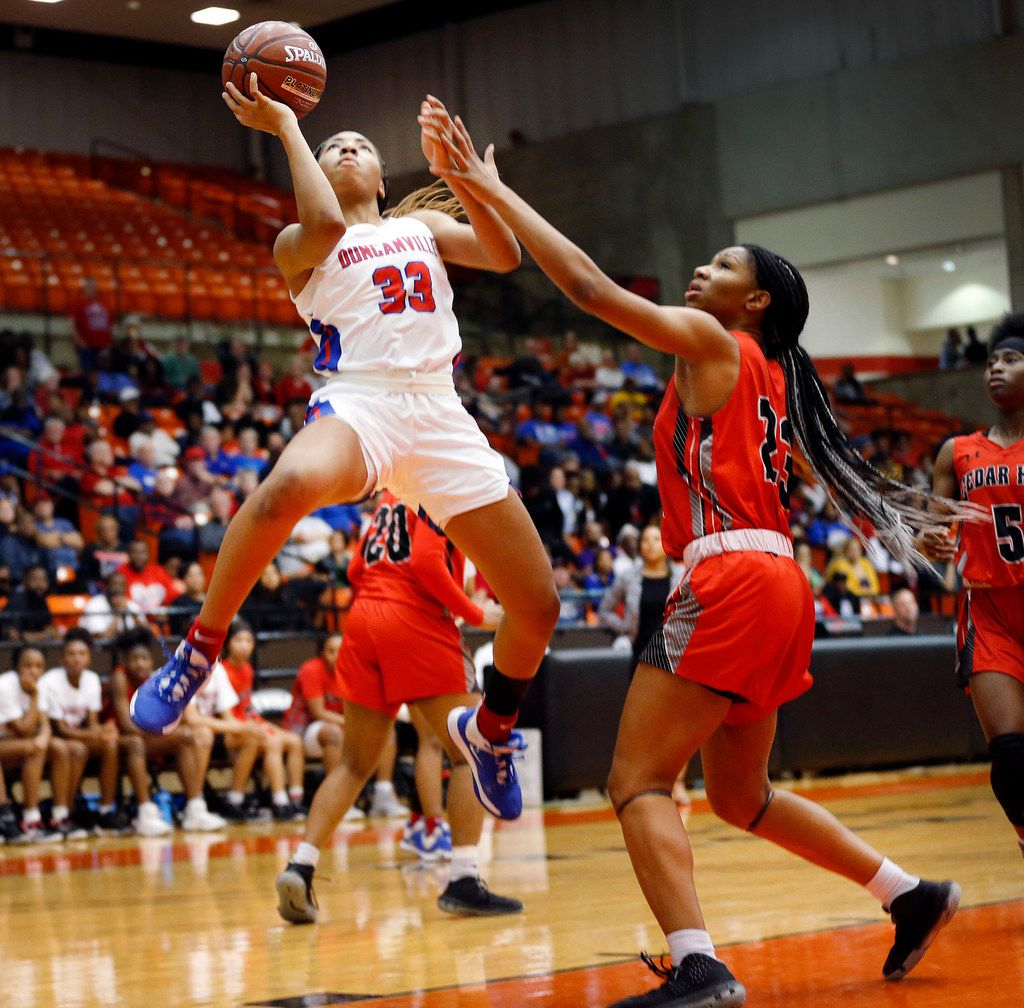 Duncanville's Nyah Wilson (33) lays up a shot past Cedar Hills' Anzhane' Hutton (23) during the first half of the Class 6A Region I championship game at Wilkerson-Greines Activity Center in Fort Worth, Saturday, February 29, 2020. (Tom Fox/The Dallas Morning News)