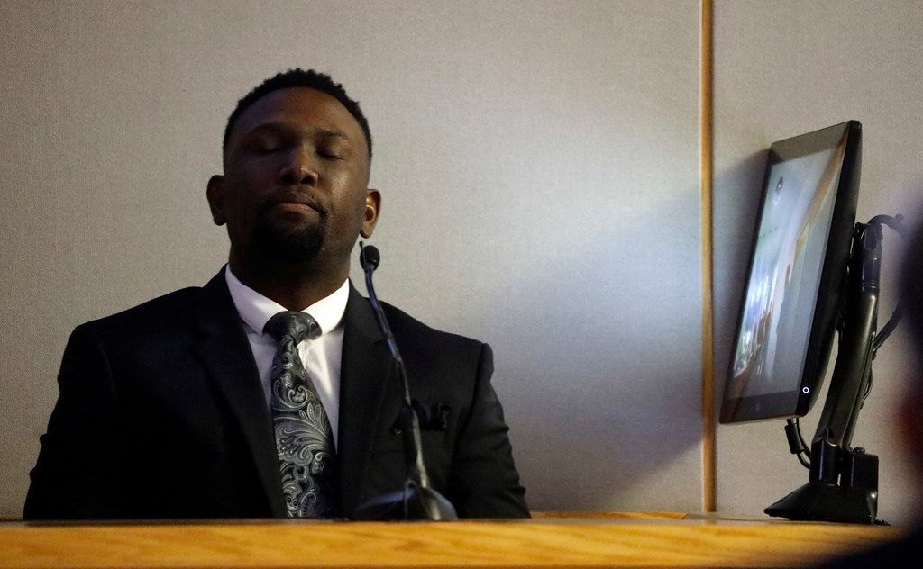 Dallas police officer Michael Lee listens and watches footage from his body camera during testimony in Amber Guyger's murder trial. Lee was one of the first responding officers to the scene and performed CPR on Botham Jean.