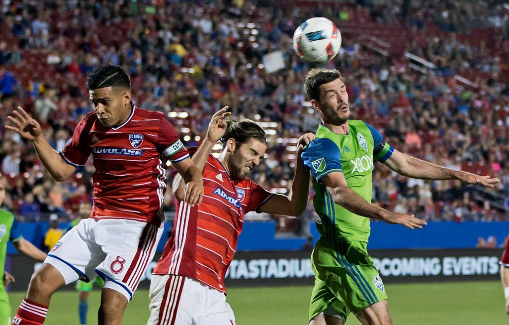 May 14, 2016; Dallas, TX, USA; Seattle Sounders FC forward Brad Evans (3) heads the ball as FC Dallas midfielder Ryan Hollingshead (12) and midfielder Victor Ulloa (8) defend during the second half  at Toyota Stadium. Mandatory Credit: Kevin Jairaj-USA TODAY Sports