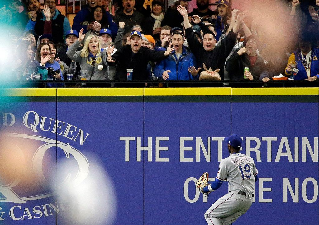 Texas Rangers left fielder Jurickson Profar and fans watch a deep fly ball from Seattle Mariners' Mitch Haniger head toward the top of the wall in the seventh inning of a baseball game Friday, April 14, 2017, in Seattle. First ruled a home run, on further review the hit was ruled a single. (AP Photo/Elaine Thompson)