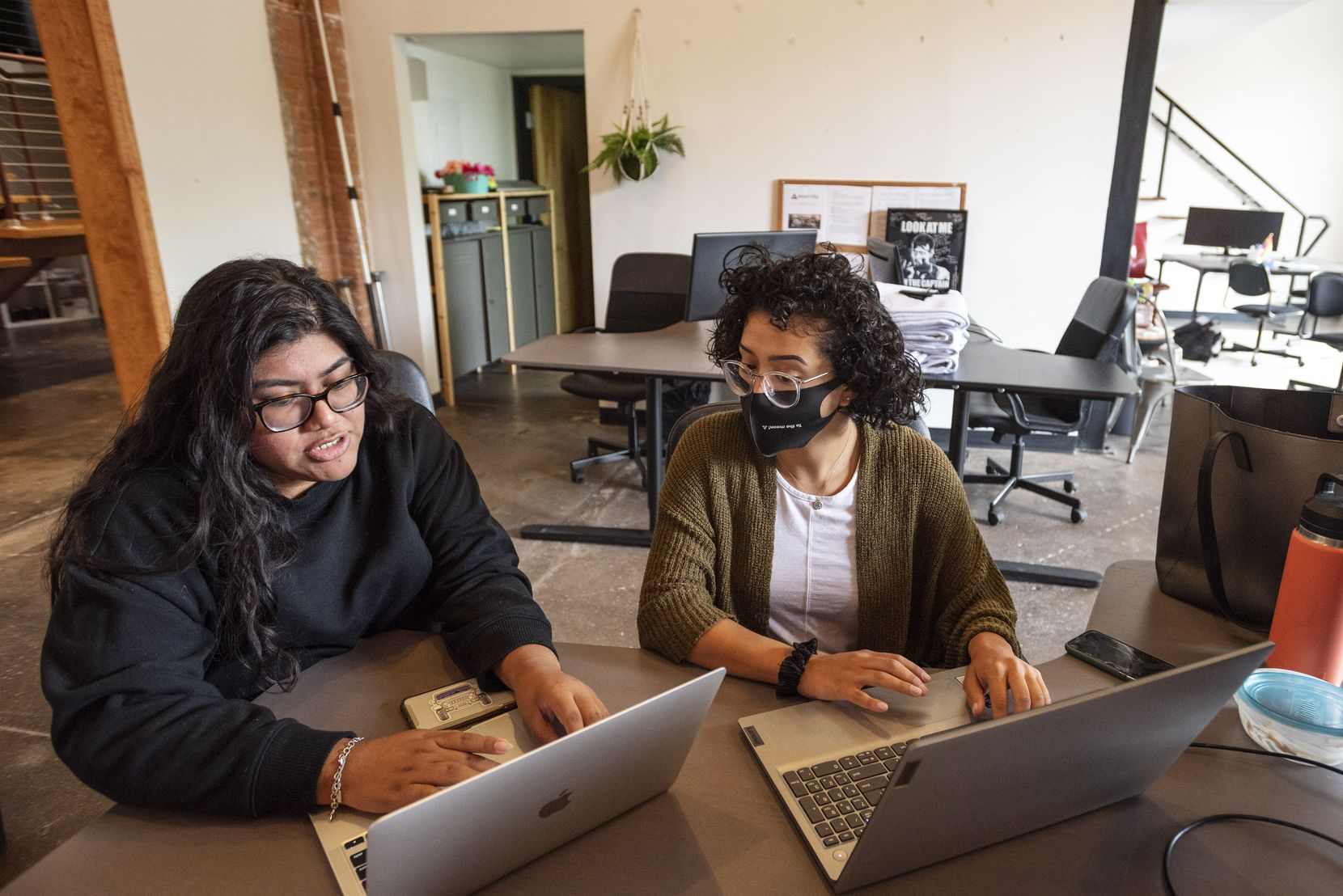 Customer experience specialists Rachel Clemente (left) and Grecia Rodriguez respond to social media direct messages with information about apartments and their locations at Smart City Apartments headquarters.