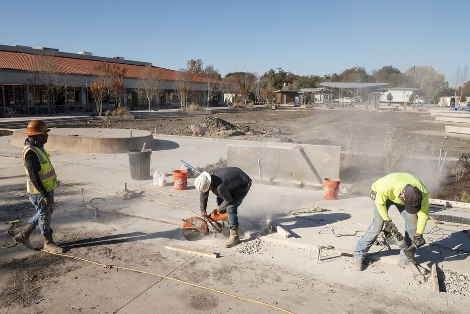 Construction workers cut through concrete as they shape the walkable areas during renovation at Hillcrest Village in Far North Dallas.