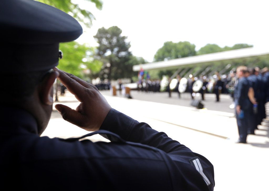 Police salute during a march and ceremony near City Hall in downtown Dallas.