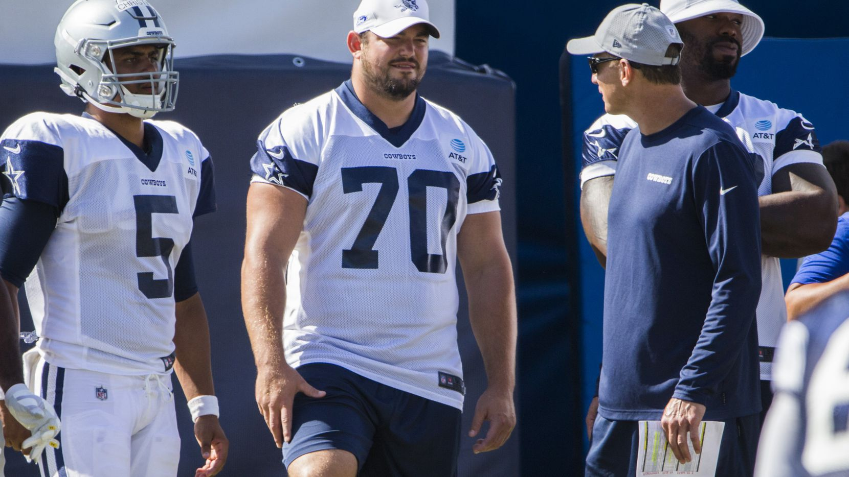 Dallas Cowboys backup quarterback Taryn Christian (5), offensive guard Zack Martin (70) and offensive tackle Tyron Smith (77) stand on the sideline during an afternoon practice at training camp in Oxnard, California on Saturday, August 3, 2019. Smith was out for a minor back injury. (Ashley Landis/The Dallas Morning News)