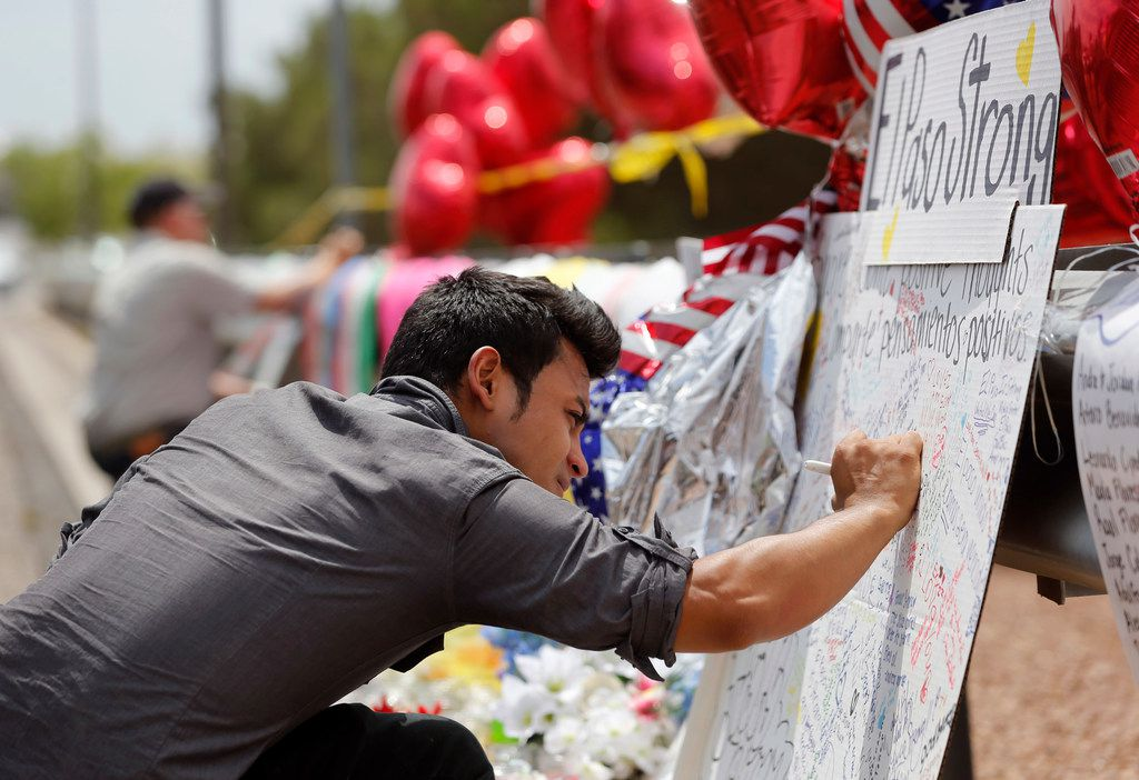 Arturo Roacho of El Paso writes a note on a poster as he visits a makeshift memorial for victims at a shopping complex near the Walmart where 22 people were killed in a mass shooting in El Paso.
