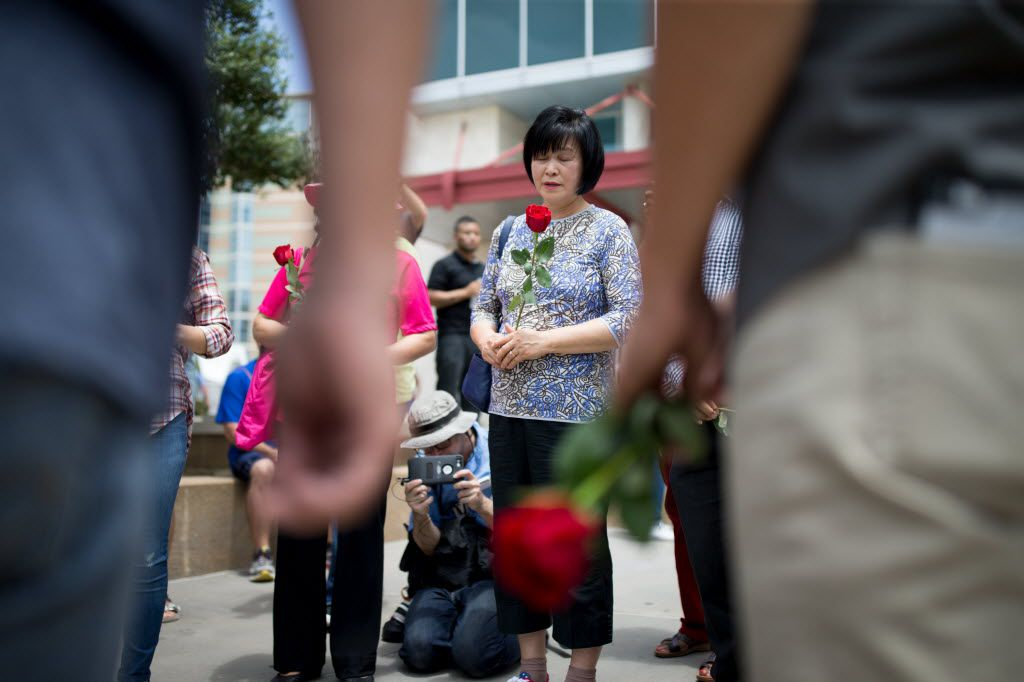 Tae Hee Yoon, of Carrollton, prays with other members of the Semihan Korean Baptist Church in Carrollton, Texas by the memorial for the slain officers at the Dallas Police headquarters on Saturday.