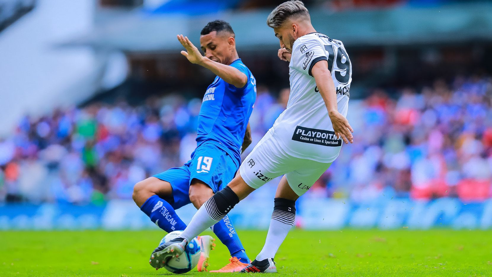 El jugador de Ciudad Juárez, Gabriel Hachen (der.) pelea el balón con el mediocampista del Cruz Azul, Víctor Yotun, durante un partido del Torneo Apertura 2019 en el Estadio Azteca.