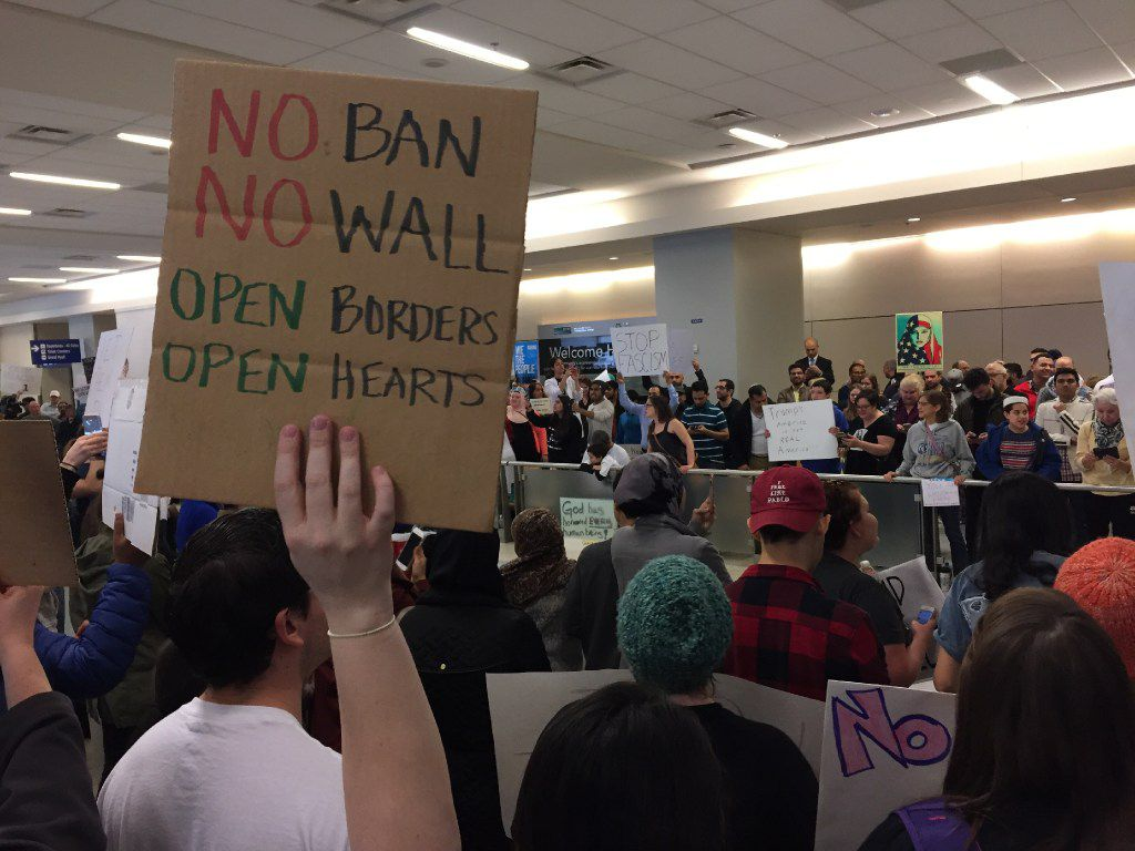 Protestors gather at the international arrivals gate at DFW Airport in Texas to orotest the restricted immigration policy on Sunday, January 29, 2017. (Louis /The Dallas Morning News)