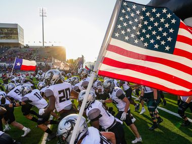 Denton Guyer wide receiver Josh Lumsden (88) carries the American flag as the teams take the field before a high school football game against Denton Ryan on Friday, Sept. 3, 2021, in Denton. (Smiley N. Pool/The Dallas Morning News)