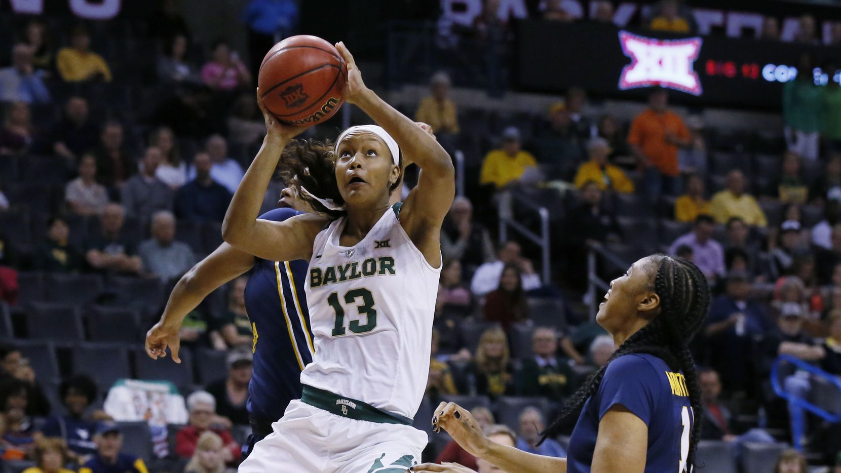 Baylor forward Nina Davis (13) shoots between West Virginia forward Teana Muldrow, left, and center Lanay Montgomery, right, in the first half of an NCAA college basketball championship game at the Big 12 Conference tournament in Oklahoma City, Monday, March 6, 2017. (AP Photo/Sue Ogrocki)