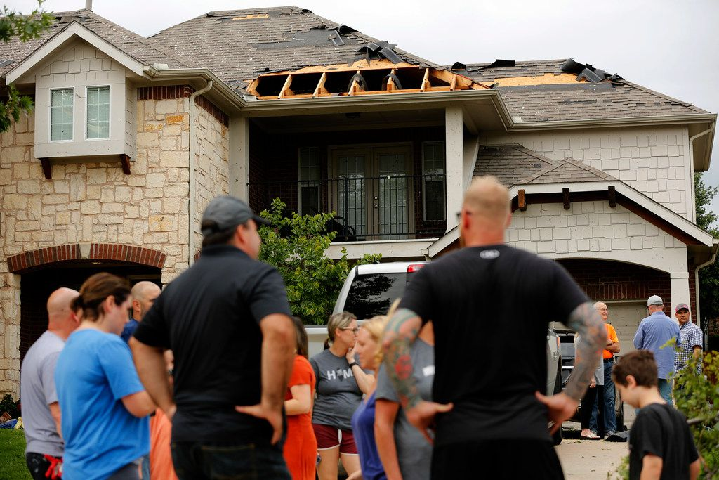 Neighbors visit outside a wind-damaged home on Oliver Dr. in North Fort Worth, after winds toppled trees and torn shingles off of homes, Wednesday, May 29, 2019. A tornado warned storm passed through the neighborhood near Heritage Trace Pkwy and N. Riverside Dr.