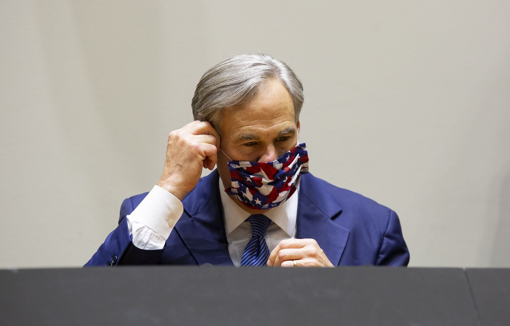 Governor Greg Abbott takes off his mask before speaking at a press conference on protest violencewith local officials on Tuesday, June 2, 2020 at City Hall in Dallas.