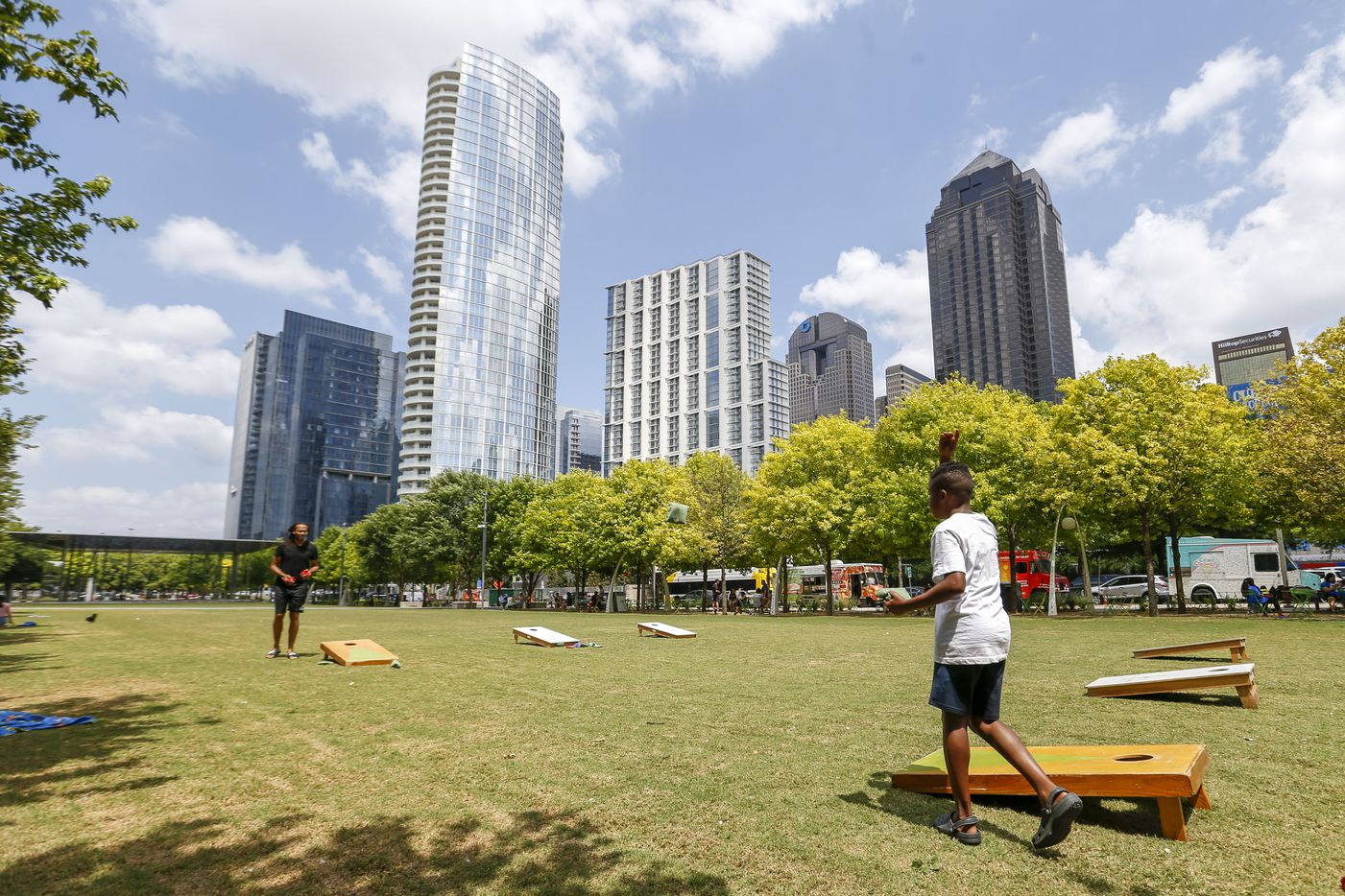 Darnell Hugee of Mesquite (left) plays cornhole with his nephew Josiah Parchman at Klyde Warren Park on Wednesday, June 23, 2021, in Dallas.