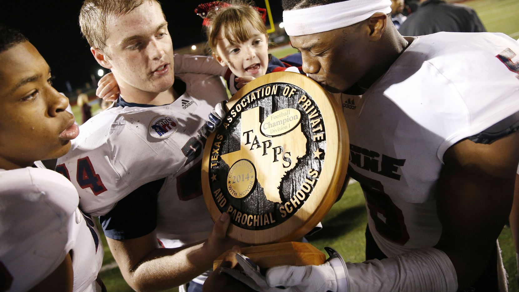 Bishop Dunne wide receiver Reginald Roberson (8) (left), offensive lineman Payton Matous (74), while holding his sister, Madi Matous, watches as defensive back Joshua Drayden (5) kisses the championship trophy after winning the TAPPS football state champ