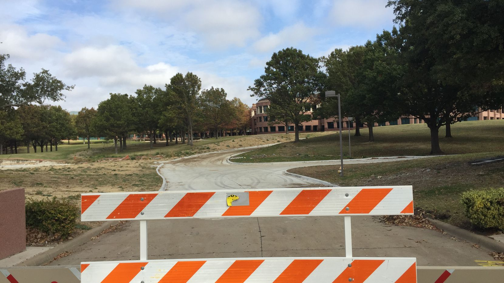 A barricade is in the long driveway to what was the main entrance of J.C. Penney's headquarters in Plano.