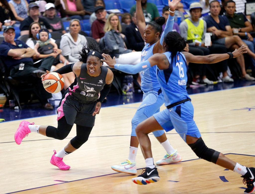 Dallas Wings guard Arike Ogunbowale (24) skips around Atlanta Dream guards Alex Bentley (20) and Tiffany Hayes (15) as she drove to the basket during the second quarter at College Park Center in Arlington, Texas, Sunday, August 25, 2019. (Tom Fox/The Dallas Morning News)