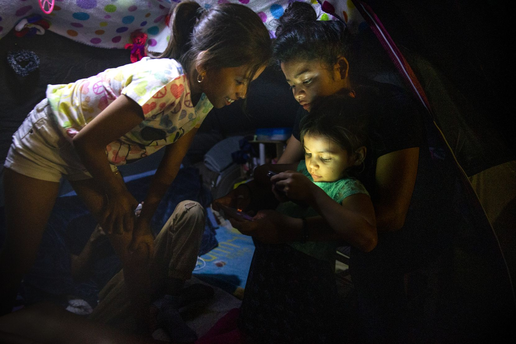 Honduran asylum-seeker Ashlee Sanchez, 14 (center) held Naomi, 6, as they and Genesis (left), 9, talked to a relative via FaceTime at the temporary tent camps in Matamoros, Mexico, on Saturday, Dec. 14, 2019.