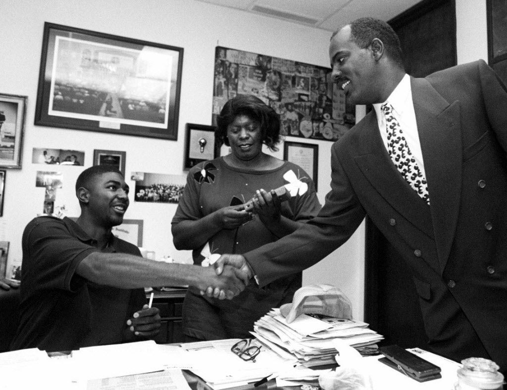 11-9-94 -- Lincoln High's Damion Walker, l,  shakes hands with Reginald Samples, athletic director of Lincoln  High School, after signing a letter of intent with TCU in the  principal's office at Lincoln High School.