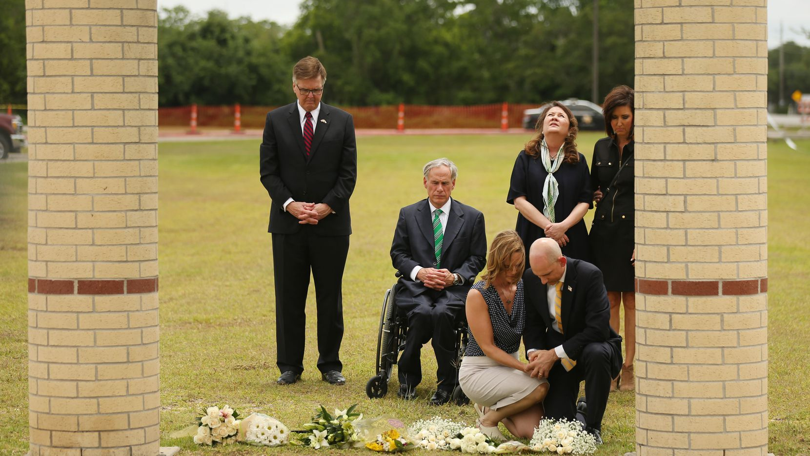 Texas Lt. Gov. Dan Patrick, Gov. Greg Abbott, and Texas first lady Cecilia Abbott pause and reflect after laying flowers at Santa Fe High School in Santa Fe, Texas Sunday May 20, 2018. On Friday morning May 18, 10 people were killed and 13 were injured after a shooting at Santa Fe High School.