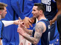 Dallas Mavericks guard JJ Redick (right) receives some pointers from teammate Luka Doncic during a second quarter timeout against the Detroit Pistons at the American Airlines Center in Dallas, Wednesday, April 21, 2021.