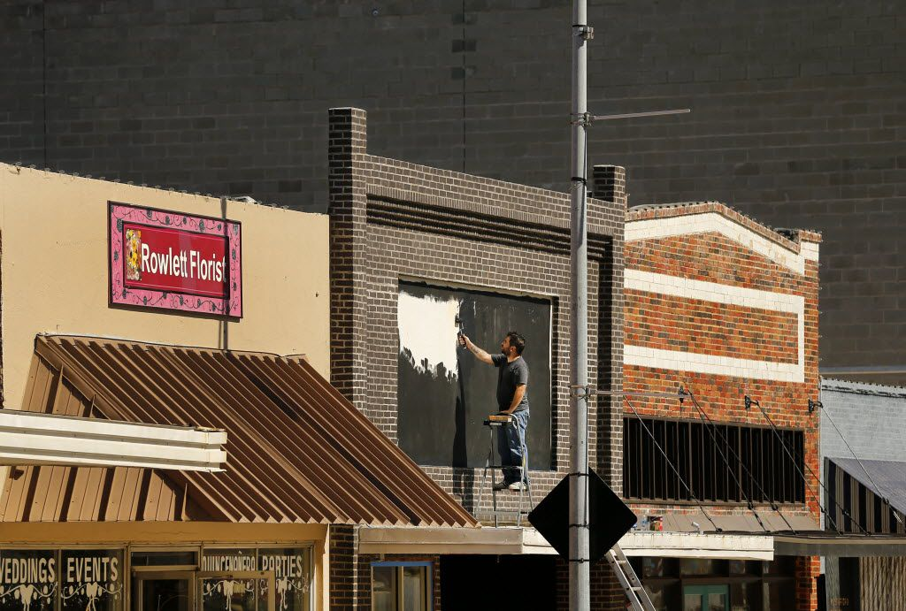 Painter and tattoo artist Lucas Cervellini paints the marquee on the new Intrinsic Smokehouse & Brewery storefront on the downtown Garland Square, Tuesday October 13, 2015. (The cinder block wall in the background is a building being constructed on the next block)