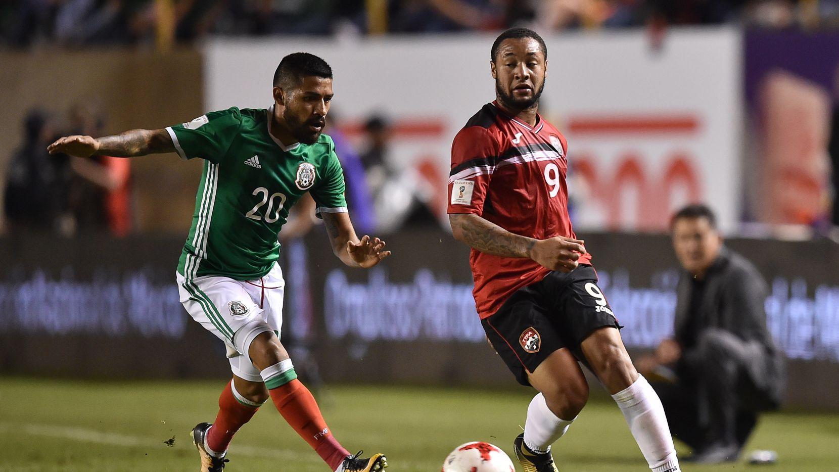 Javier Aquino (izq.) de México disputa el balón con el delantero de Trinidad y   Tobago Shahdon Winchester durante un partido clasificatorio para el Mundial de Rusia 2018.