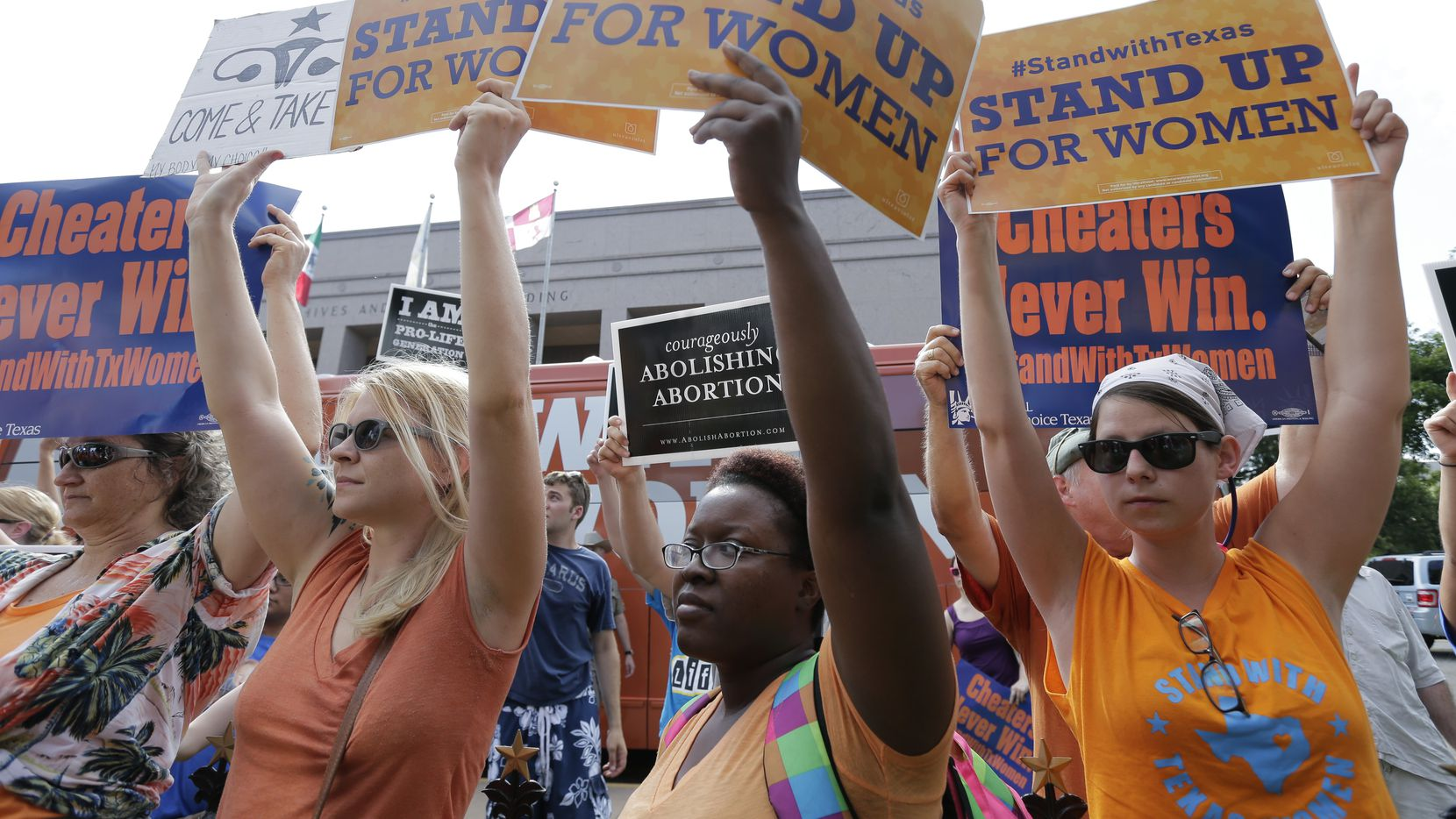 FILE - In this July 9, 2013, file photo, opponents and supporters of an abortion bill hold signs near a news conference outside the Texas Capitol, in Austin, Texas. A sharply divided Supreme Court on Tuesday, Nov. 19, 2013, allowed Texas to continue enforcing abortion restrictions that opponents say have led more than a third of the state's clinics to stop providing abortions. (AP Photo/Eric Gay, File)