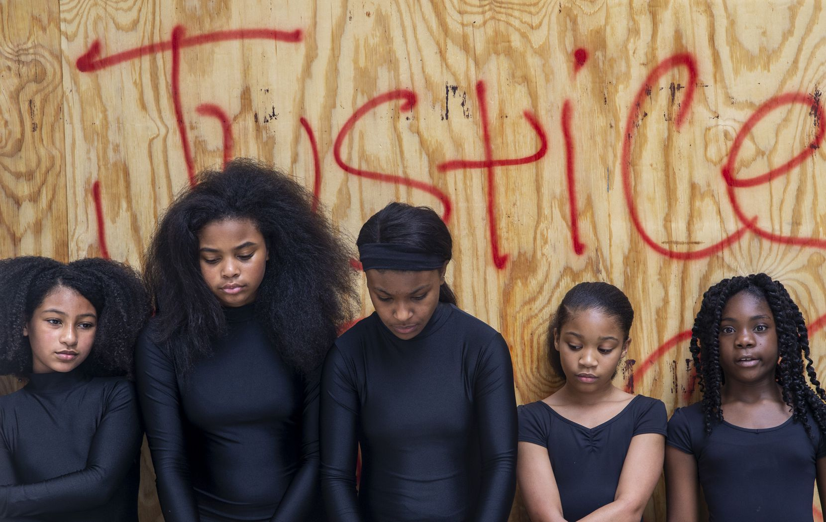 """Lexi Anderson (from left), 10; Reign Villegas, 13; Michaia Thomas, 12; Kennedy Williams, 11; and Jordin Willis, 10, dancers with Elev8ed Elites Dance and Cheer Company, stand in front of the words """"No Justice, No Peace"""" on a boarded-up building on Commerce Street downtown. Their director, Shantrail White, took them to survey graffiti June 1 after a weekend of protests."""