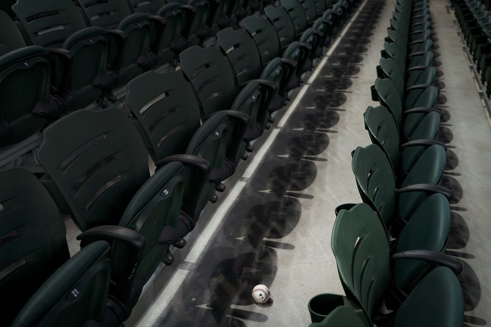 A baseball rests among empty rows of seats after being fouled off by a batter in an intrasquad game during Texas Rangers Summer Camp at Globe Life Field on Thursday, July 16, 2020.