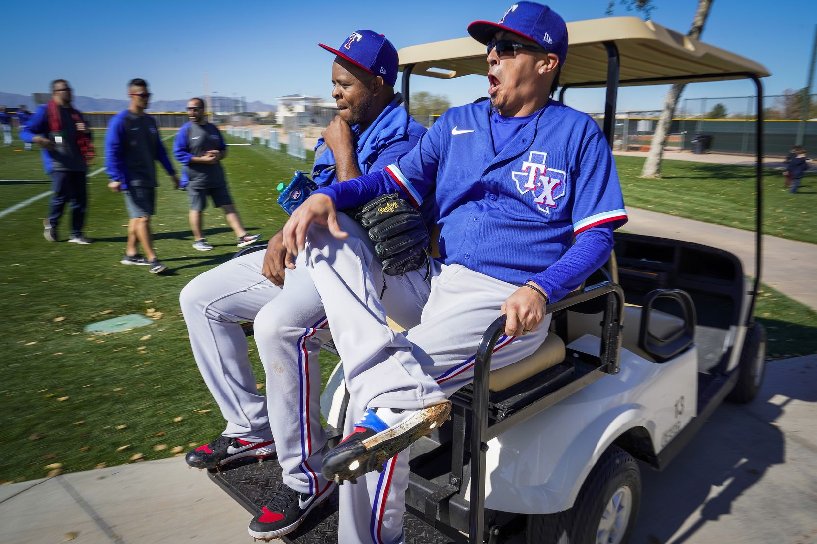 Texas Rangers pitcher Jesse Chavez (30) laughs with pitcher Edinson Volquez (36) as they ride in a golf cart following a spring training workout at the team's training facility on Thursday, Feb. 13, 2020, in Surprise, Ariz.