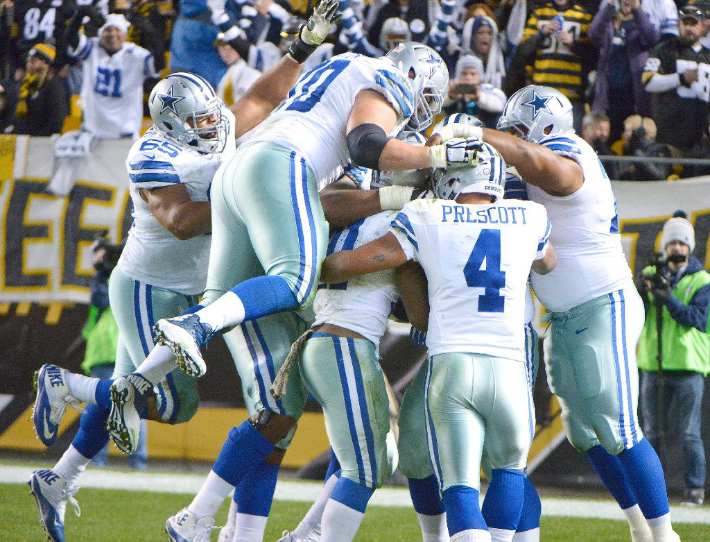 Dallas Cowboys quarterback Dak Prescott (4) and the rest of the offense swarm around running back Ezekiel Elliott (21) after he scored the game-winning touchdown as the Dallas Cowboys beat the Pittsburgh Steelers 35-30 on Sunday, Nov. 13, 2016 at Heinz Field in Pittsburgh, Pa. (Max Faulkner/Fort Worth Star-Telegram/TNS)