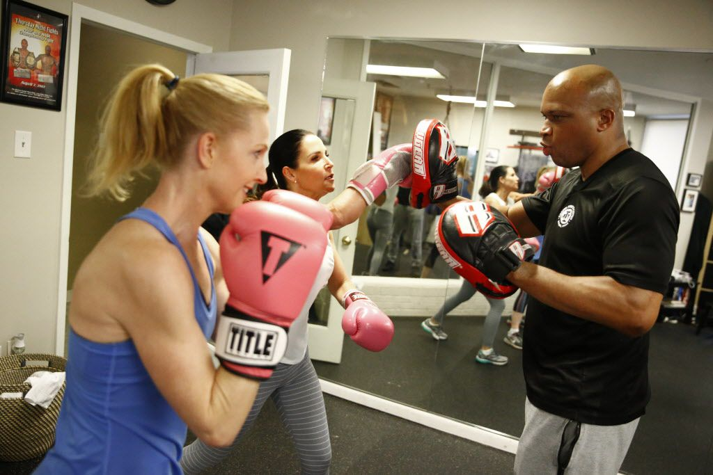 Meridan Zerner (from left) and Cass Wright practice punching with boxing trainer Derrick James at The Cooper Fitness Center in Dallas on Jan. 10, 2018 .  James trained Errol Spence, IBF welterweight champion. (Nathan Hunsinger/The Dallas Morning News)