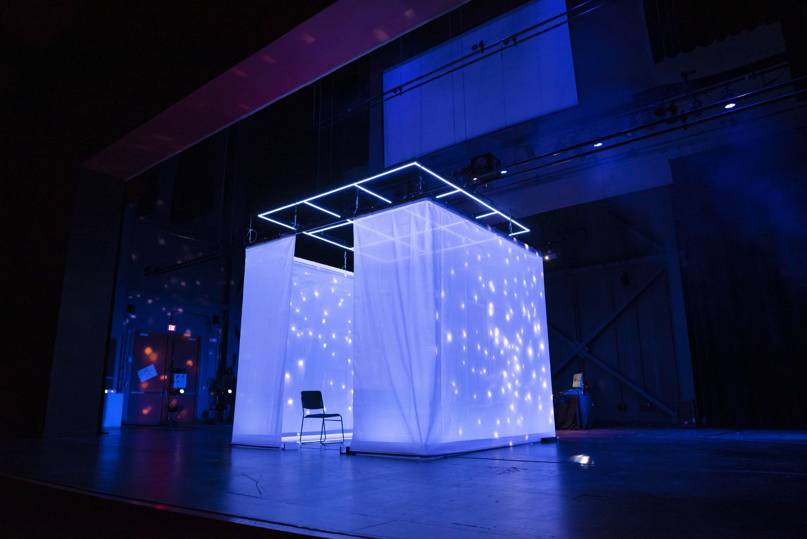 "A curtained-off square serves as projection screen and audience pod in ""The Cube"" at the Latino Cultural Center."