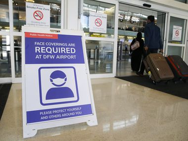A sign notifying travelers to wear a mask as people make their way into Terminal D at DFW International Airport on Monday, November 16, 2020.