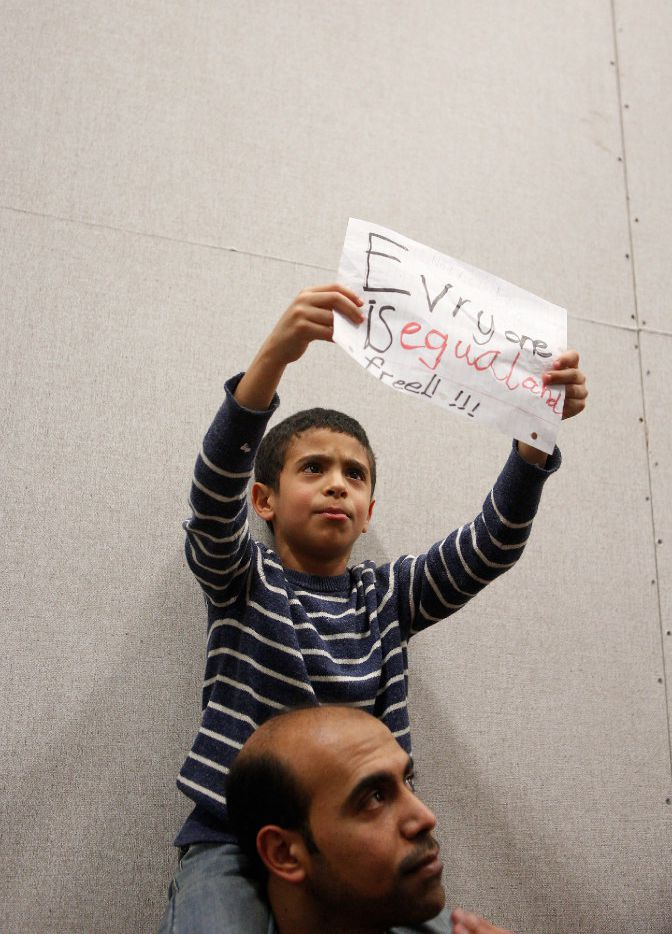 Mahmoud and his son Nour, 7, join the protest to denounce President Donald Trump's executive order that bans certain immigration, at Dallas-Fort Worth International Airport on January 28, 2017 in Dallas, Texas. President Trump signed the controversial executive order that halted refugees and residents from predominantly Muslim countries from entering the United States.